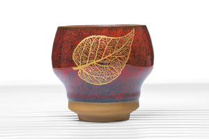 High Sided Footed Tea Bowl With Crimson Speckled Glaze And Golden Leaf Pattern
